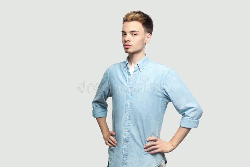 Retrato do homem novo consider?vel satisfeito orgulhoso em claro - posi??o azul da camisa com m?os na cintura e vista da c?mera c imagens de stock