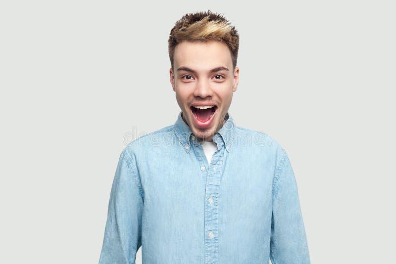 Retrato do homem novo considerável surpreendido em claro - posição azul da camisa e vista da câmera com expressão surpreendida da imagem de stock royalty free
