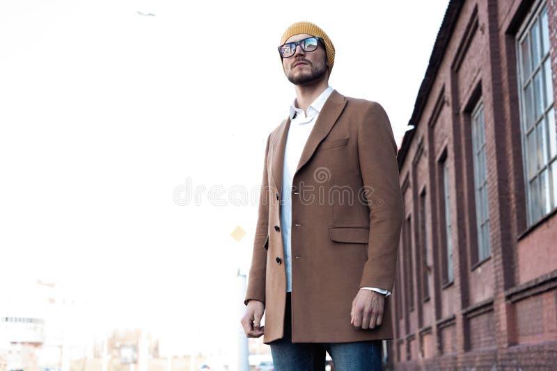 Retrato do homem novo consider?vel ? moda nos vidros com a cerda que est? fora Revestimento e camisa vestindo do homem fotografia de stock