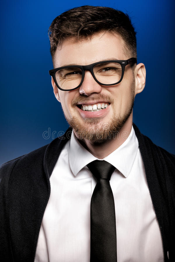 Retrato do homem novo de sorriso considerável com vidros e a camisa branca no fundo azul foto de stock