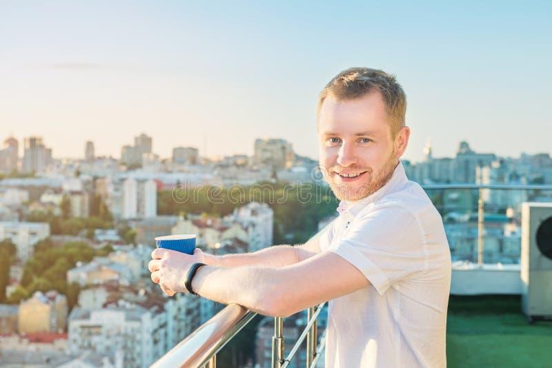 Retrato do homem novo de sorriso que está no balcão alto da construção da elevação com o copo de papel com bebida quente, vista i foto de stock royalty free