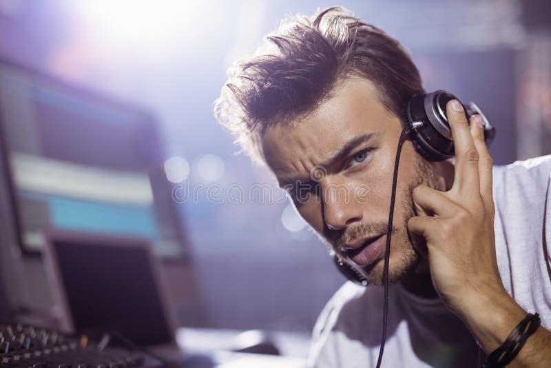 Retrato do homem novo DJ com os fones de ouvido no clube noturno fotografia de stock royalty free
