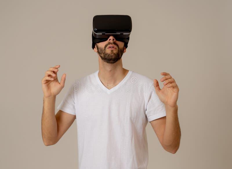 Retrato do homem novo entusiasmado e surpreendido que veste os auriculares da realidade virtual que exploram o mundo 3D fotos de stock