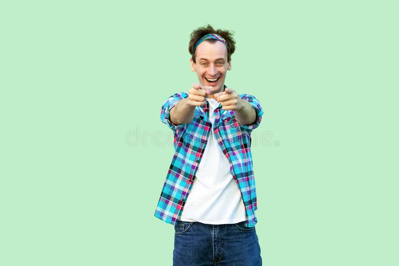 Retrato do homem novo entusiasmado na posi??o quadriculado azul ocasional da camisa e da faixa com sorriso toothy, olhando e apon imagens de stock royalty free