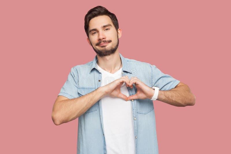Retrato do homem novo farpado considerável do smiley feliz na posição azul da camisa do estilo ocasional com gesto de mão do amor fotos de stock royalty free