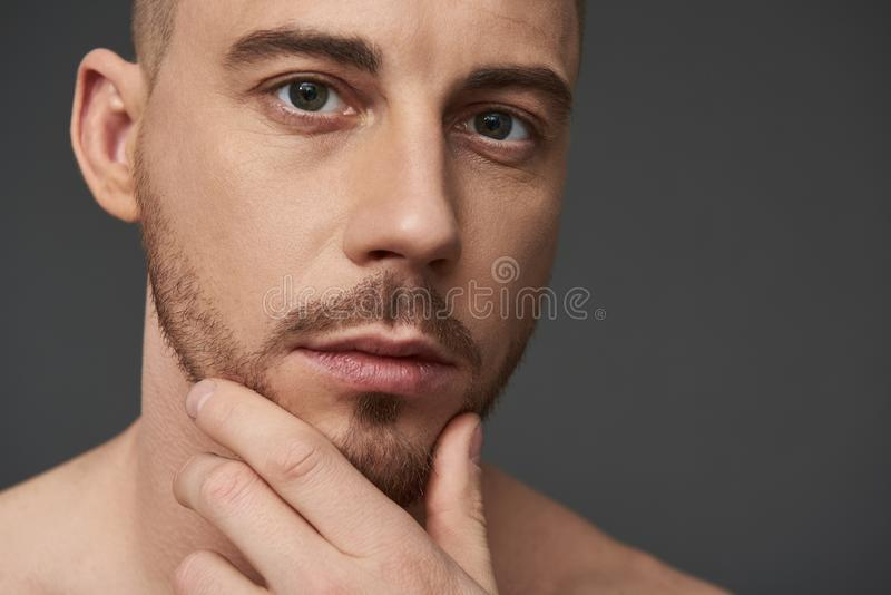 Retrato do homem novo farpado consider?vel em seguida que tem o chuveiro que olha a c?mera fotos de stock royalty free