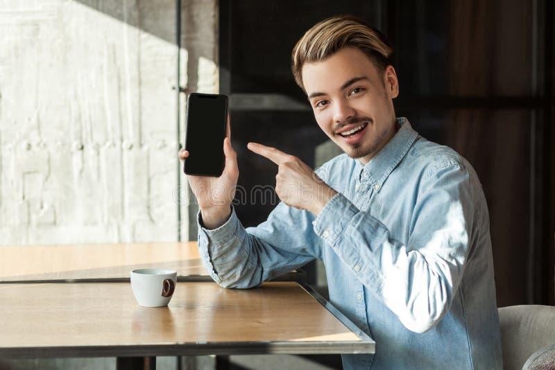 Retrato do homem novo farpado positivo feliz na camisa azul da sarja de Nimes que senta-se no café, guardando o telefone e aponta foto de stock