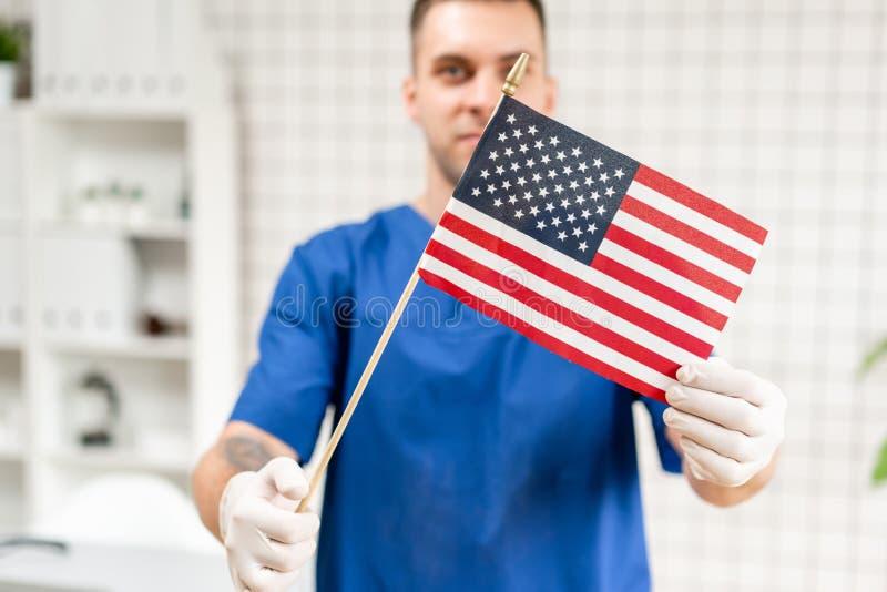 Retrato do homem novo feliz e bem sucedido do doutor que guarda a bandeira americana nas mãos, na clínica médica foto de stock