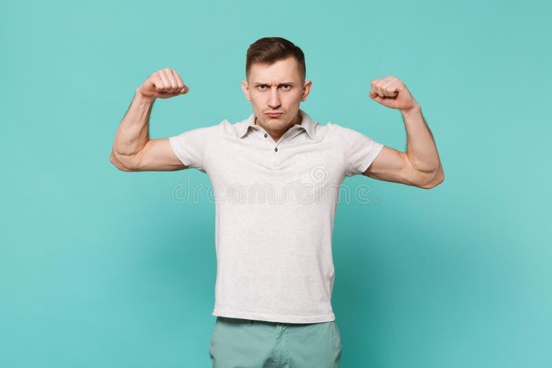 Retrato do homem novo forte na roupa ocasional que está, mostrando o bíceps, músculos isolados na parede azul de turquesa fotografia de stock