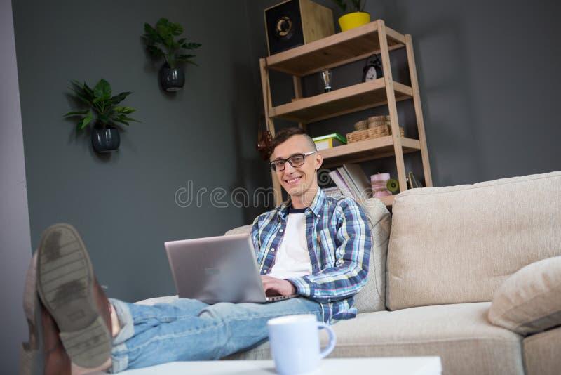 Retrato do homem novo do freelancer que senta-se na introdução do sofá no portátil fotos de stock