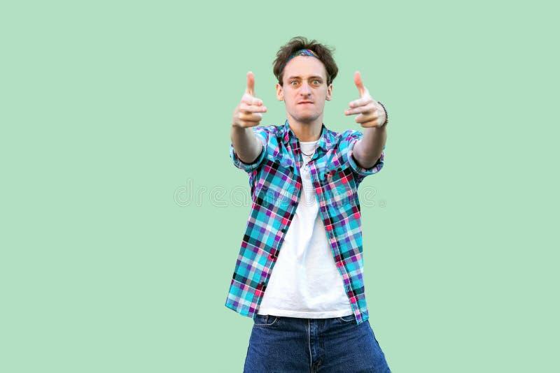 Retrato do homem novo irritado na posi??o quadriculado azul ocasional da camisa e da faixa com gesto de m?o da arma da pistola, o foto de stock royalty free
