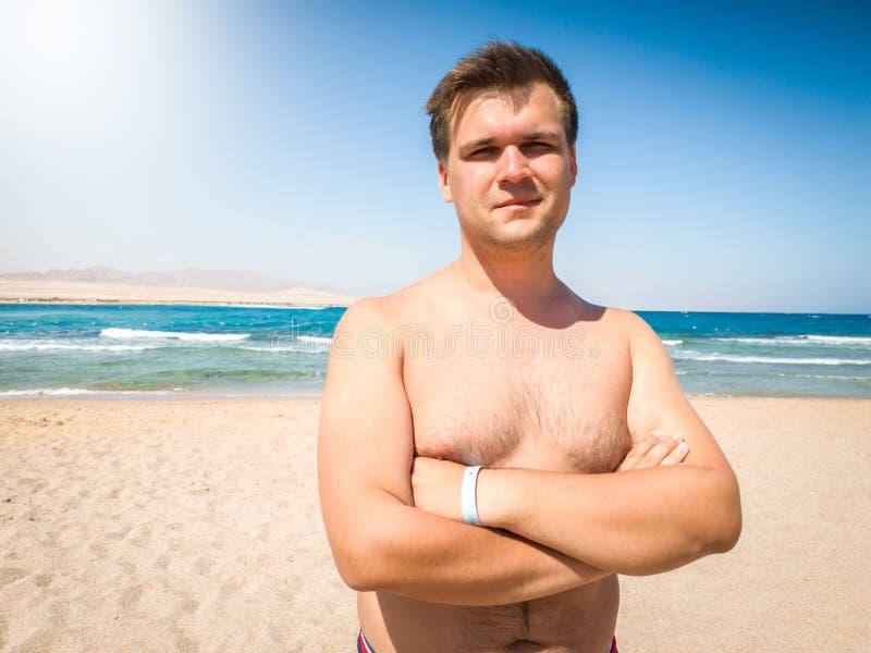 Retrato do homem novo muscular de sorriso que levanta na praia contra o mar e o céu azul imagens de stock royalty free