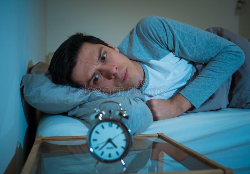 Retrato do homem novo na cama que olha fixamente no despertador que tenta dormir sentindo forçado e sem sono fotos de stock royalty free