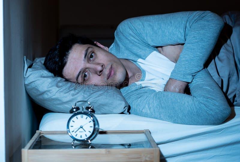 Retrato do homem novo na cama que olha fixamente no despertador que tenta dormir sentindo forçado e sem sono fotografia de stock