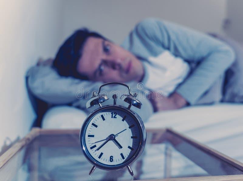Retrato do homem novo na cama que olha fixamente no despertador que tenta dormir sentindo forçado e sem sono imagem de stock