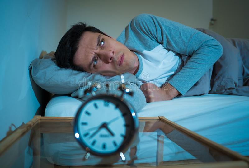 Retrato do homem novo na cama que olha fixamente no despertador que tenta dormir sentindo forçado e sem sono imagem de stock royalty free
