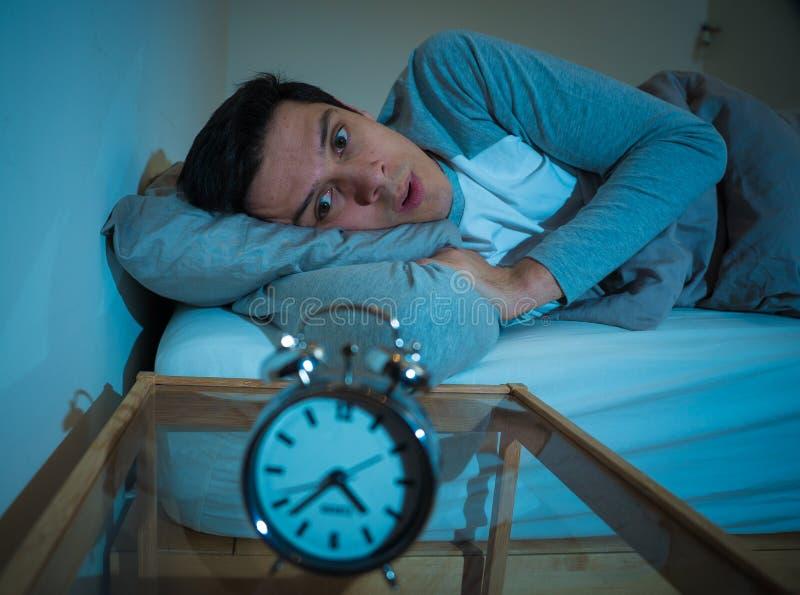 Retrato do homem novo na cama que olha fixamente no despertador que tenta dormir sentindo forçado e sem sono foto de stock royalty free
