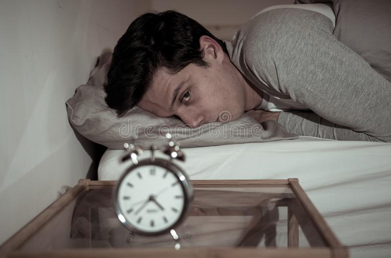 Retrato do homem novo na cama que olha fixamente no despertador que tenta dormir sentindo forçado e sem sono imagens de stock royalty free
