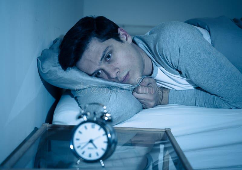Retrato do homem novo na cama que olha fixamente no despertador que tenta dormir sentindo forçado e sem sono fotos de stock