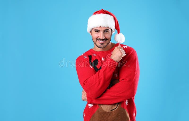 Retrato do homem novo na camiseta do Natal e no chapéu de Santa na luz - azul imagem de stock royalty free