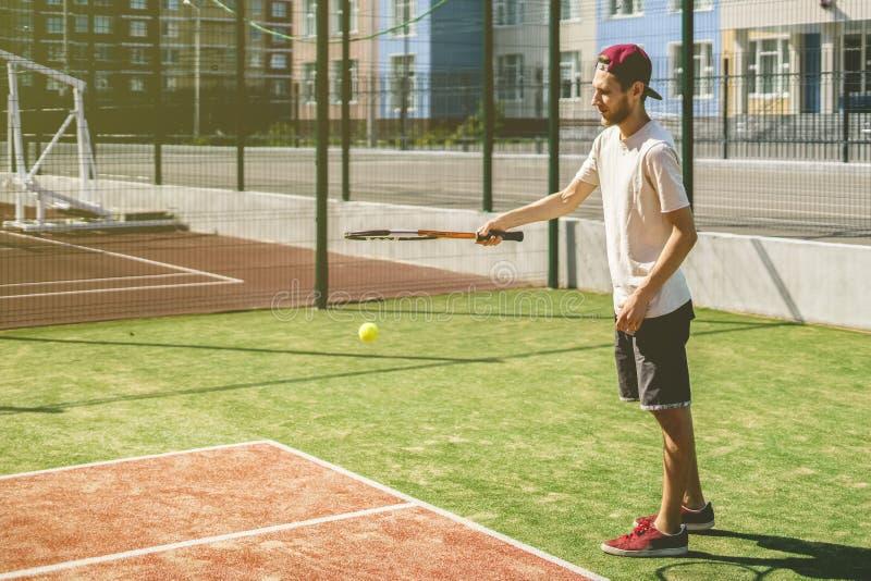 Retrato do homem novo no campo de tênis da escola do terreno do verão foto de stock