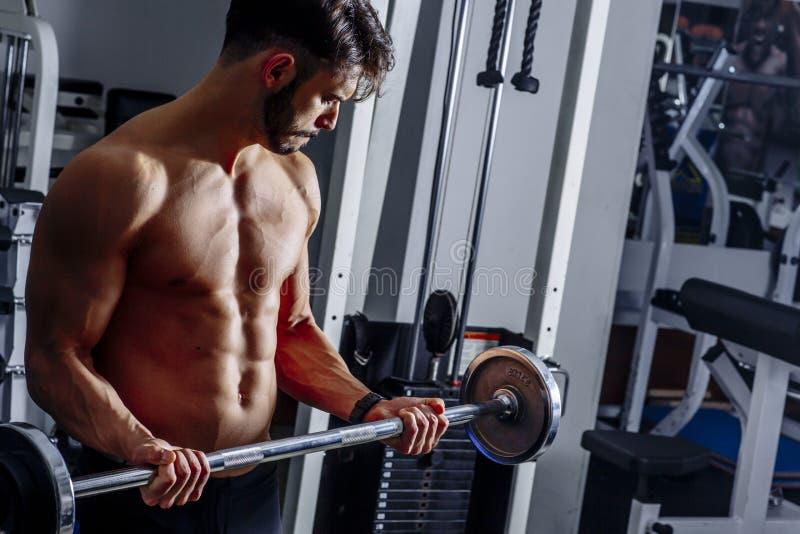Retrato do homem novo que dobra os músculos com o barbell no gym fotografia de stock royalty free