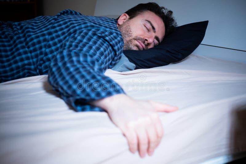 Retrato do homem novo que dorme em sua cama foto de stock royalty free