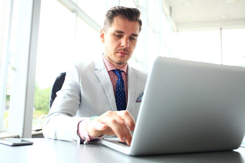 Retrato do homem novo que senta-se em sua mesa no escritório imagem de stock royalty free