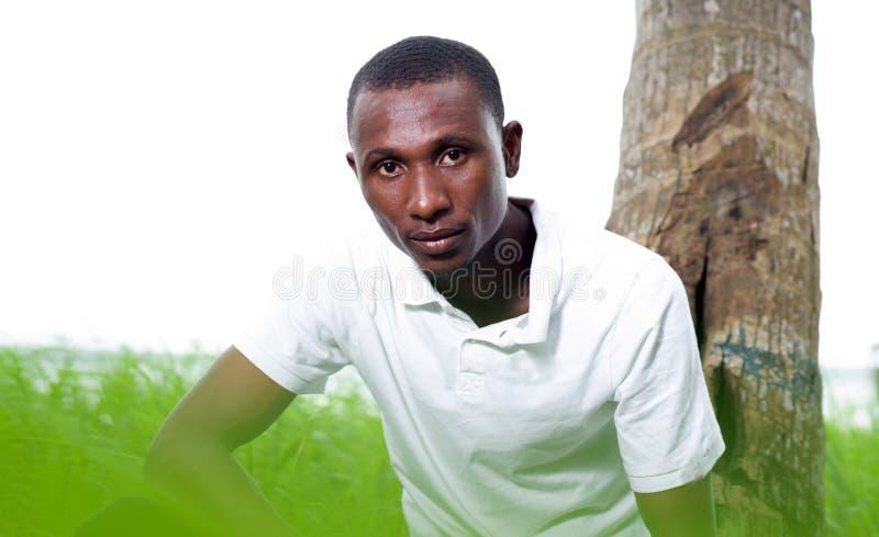 Retrato do homem novo que senta-se na grama fotografia de stock royalty free