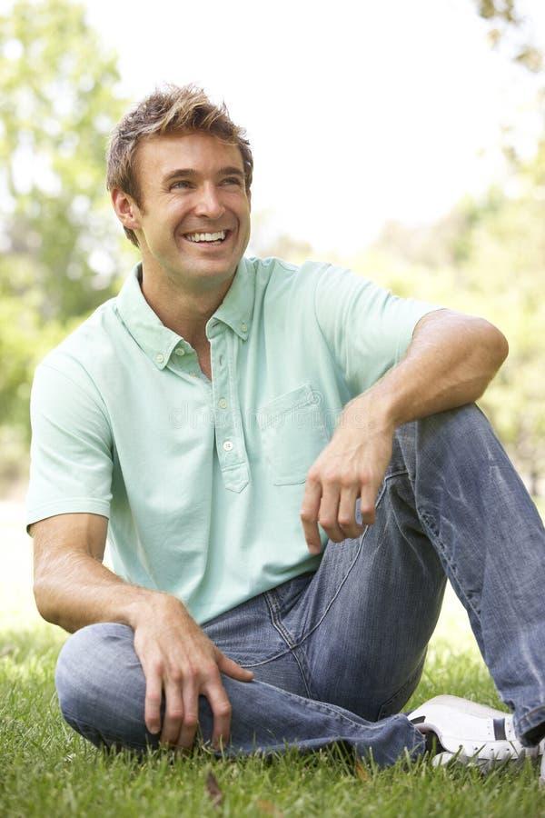 Retrato do homem novo que senta-se no parque fotografia de stock