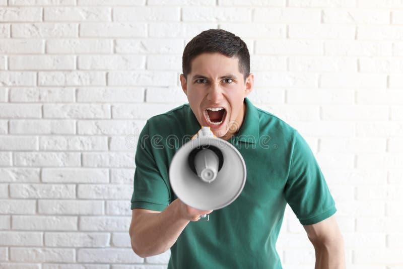 Retrato do homem novo que usa o megafone fotos de stock royalty free