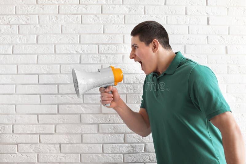 Retrato do homem novo que usa o megafone perto da parede de tijolo fotografia de stock