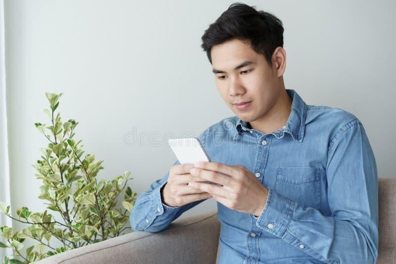 Retrato do homem novo que veste a camisa azul que olha com smartphone e que senta-se em seu sofá no escritório fotografia de stock