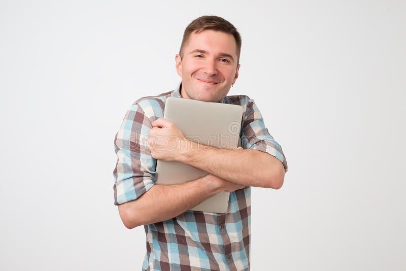 Retrato do homem novo seguro que guarda o portátil que está contra a parede branca fotos de stock royalty free