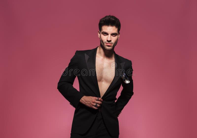 Retrato do homem novo 'sexy' que abotoa seu tux preto imagem de stock royalty free