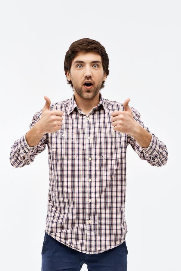 Retrato do homem novo surpreendido considerável, na câmera que mostra o thum foto de stock