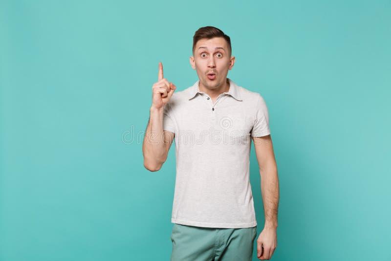 Retrato do homem novo surpreendido na roupa ocasional que mantém o indicador com grande ideia nova isolado na turquesa azul imagem de stock