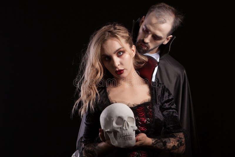 Retrato do homem novo vestido acima como Dracula que olha o pescoço de sua mulher do vampiro fotos de stock
