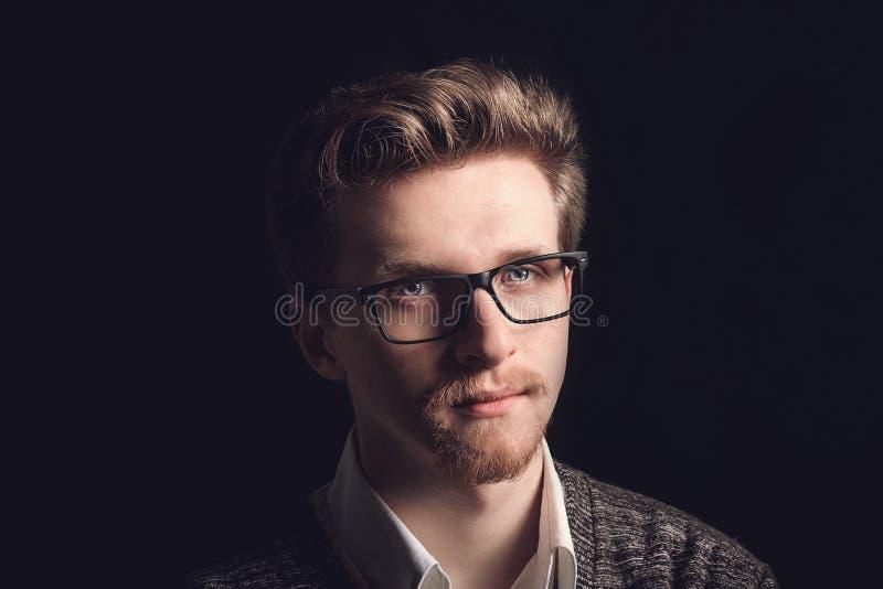 Retrato do homem ocasional novo com vidros que sorri na frente da câmera Homem considerável novo na camisa e nos vidros da marinh fotografia de stock royalty free