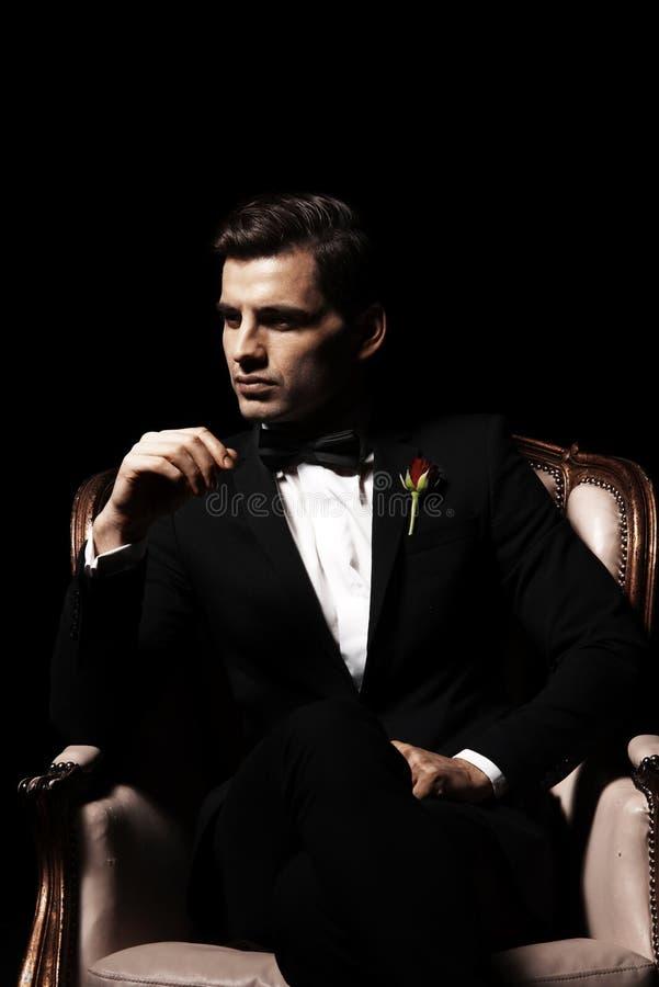 Retrato do homem que que senta-se na cadeira fotografia de stock