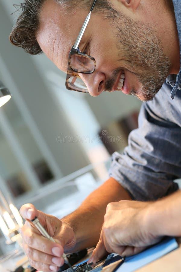 Retrato do homem que repara o smartphone fotos de stock royalty free