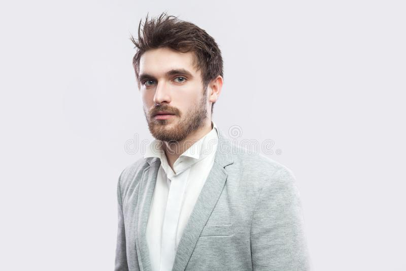 Retrato do homem sério farpado considerável com cabelos marrons e da barba na camisa branca e na posição cinzenta ocasional do te foto de stock