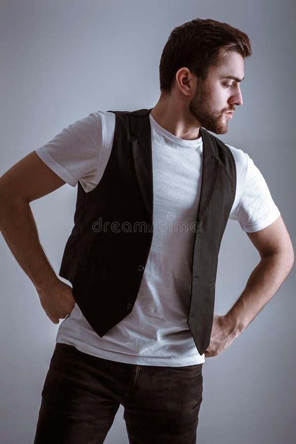 Retrato do homem sério novo considerável na camisa branca no fundo cinzento imagens de stock