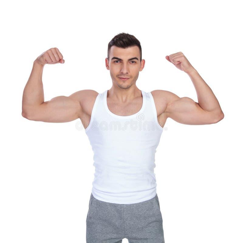 Retrato do homem 'sexy' muscular na camiseta que dobra seu bíceps fotografia de stock