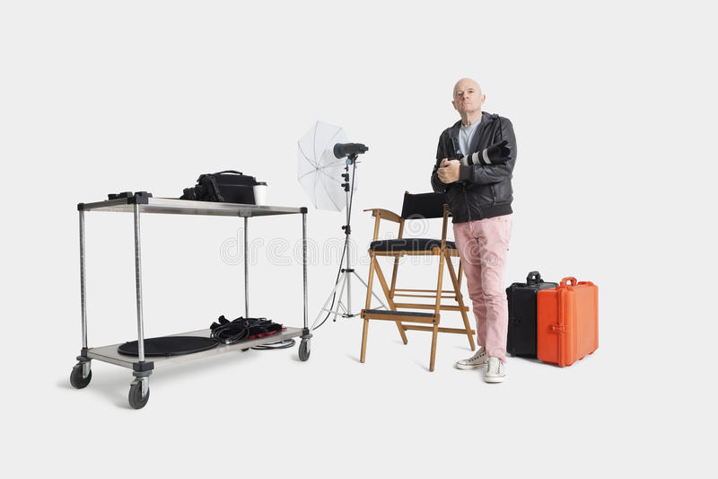 Retrato do homem superior com câmera e dos equipamentos que estão no estúdio do fotógrafo imagens de stock royalty free
