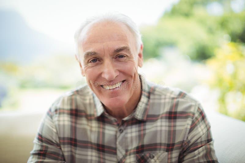 Retrato do homem superior de sorriso que senta-se no sofá na sala de visitas foto de stock