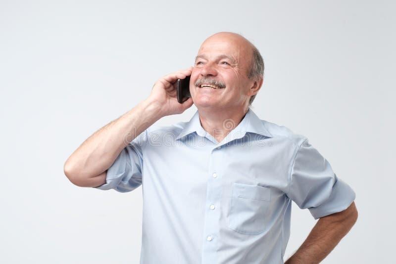Retrato do homem superior europeu feliz que fala no telefone e no sorriso fotos de stock royalty free