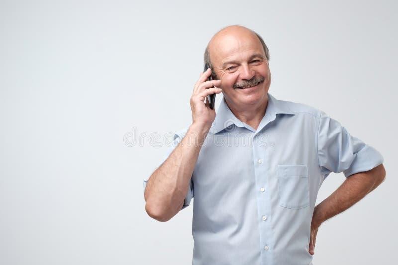Retrato do homem superior europeu feliz que fala no telefone e no sorriso foto de stock royalty free