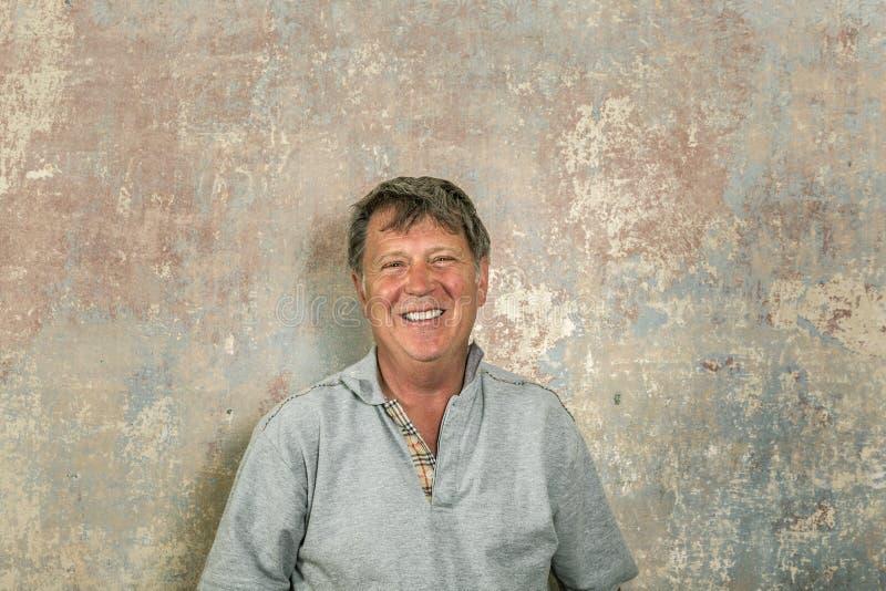 Retrato do homem superior na frente da parede velha suja foto de stock royalty free