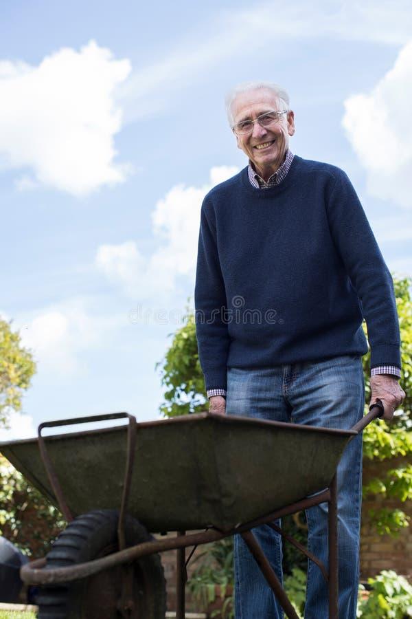 Retrato do homem superior que empurra o carrinho de mão enquanto jardinando foto de stock